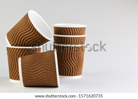 Disposable paper cup of coffee on grey background. Package for drinks. #1571620735