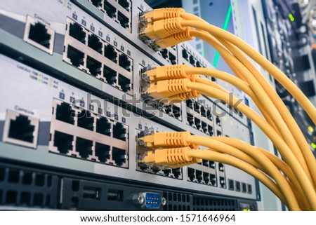 A bunch of yellow communication cables connect to the router interfaces. Telecommunication equipment is in the server room of the data center. Technology concept.  Internet utp wires. #1571646964