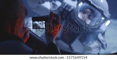 Medium close-up of a male astronaut filming his spacewalking crewmate from inside a spacecraft #1571649154