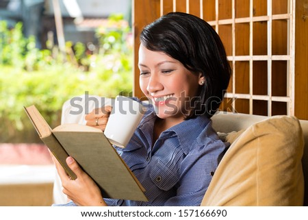Student - Young asian woman or girl sitting on a sofa with a cup of coffee reading a book, she is learning #157166690
