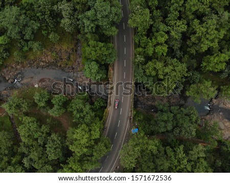 drone shot of the Mysterios road going throughout the dense forest captured through drone . curvy road in middle of the the forest . beautiful destinations of India . Maharashtra  #1571672536