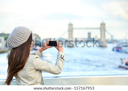 London woman tourist taking photo on Tower Bridge with mobile smart phone camera. Girl enjoying view over the River Thames, London, England, Great Britain. United Kingdom tourism concept.