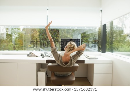 Young woman stretching at desk of office at home #1571682391