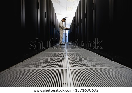 Computer technician working in server room in Cape Town, South Africa #1571690692
