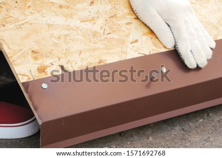 Nailing and hammering a sheet of roofing iron. #1571692768