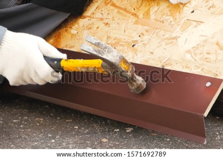 Nailing and hammering a sheet of roofing iron. #1571692789