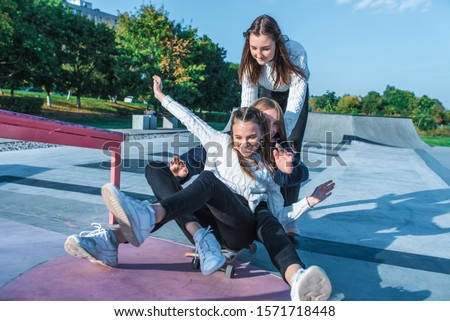 Three teenage girls teenagers ride skateboard, happy have fun playing and laughing, summer sports ground, in warm sweaters fall afternoon. Free space for copy text. Emotions happiness delight #1571718448
