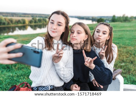 Three teenage girls, teenagers in summer city have rest after school college, hands smartphone, selfie picture video call online application on social networks. Happy smiling. Casual clothes, sweater #1571718469