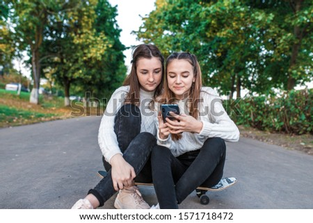 Two teenage girls teenagers, best girlfriends, summer park, sitting skateboard, watching funny videos smartphone, happy smiling, casual clothes, autumn day. Concept relaxation after school college #1571718472