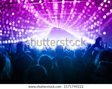 Concert stage inside a big venue, people are visible waving and clapping. Only silhouettes are visible before stage spotlights. #1571749222
