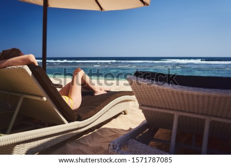 White sand beach with chear and umbrellas. Young female relaxing under umbrella shadow                                #1571787085