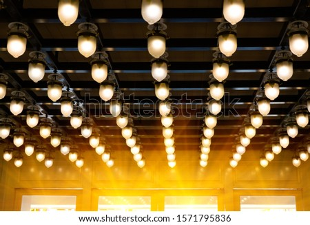 Lamps on row on the wooden ceiling.illuminate is throw the light upon in the reception hall room.Classic lighting interior design with sunlight effect from the glass of window. #1571795836
