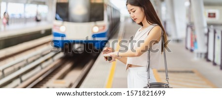 Banner, web page or cover template of Asian woman passenger using social network via smart mobile phone in subway train when traveling in big city,japanese,chinese,Korean lifestyle concept #1571821699