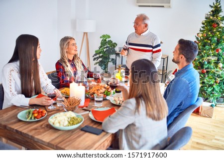 Beautiful family meeting smiling happy and confident. Speaking speech eating roasted turkey celebrating Christmas at home #1571917600