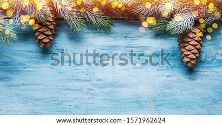 Fir covered with snow and Christmas decor on a blue wooden table. Christmas or New Year holiday background. Top view. #1571962624
