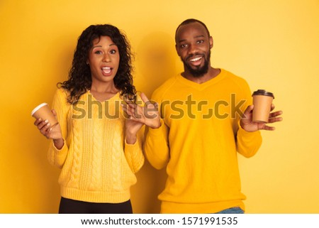 Young emotional african-american man and woman in bright casual clothes on yellow background. Beautiful couple. Concept of human emotions, facial expession, relations, ad. Drinking coffee together. #1571991535