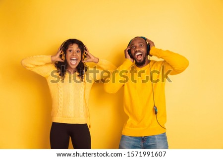 Young emotional african-american man and woman in bright casual clothes posing on yellow background. Beautiful couple. Concept of human emotions, facial expession, relations, ad. Listen to music, sing #1571991607
