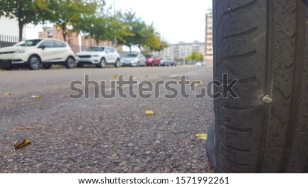 Car tire deflated because a nail is pounding the rubber. Closeup #1571992261