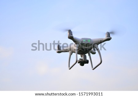 beautiful white drone flying in bluesky day for take aerial photo by small camera.