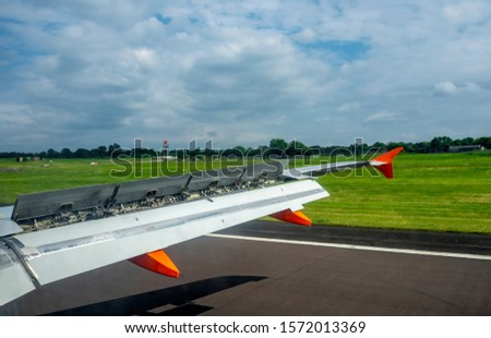 Aircraft wing with extended flaps and spoilers while landing on the runway in the airport #1572013369