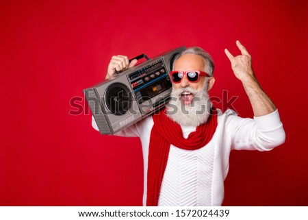 Portrait od foolish santa in eyewear eyeglasses holding boombox showing heavy metal sign wearing white pullover isolated over red background #1572024439