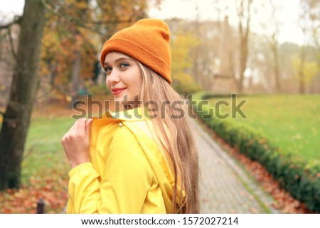 Happy young woman in autumn park #1572027214