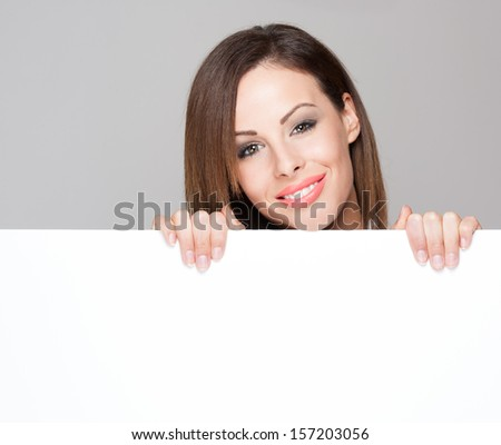 Portrait of a fashionable brunette beauty with blank white billboard for text. #157203056