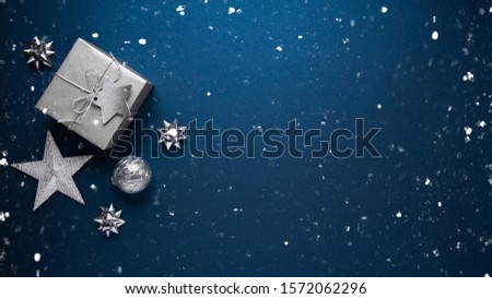 Merry Christmas and Happy Holidays greeting card, frame, banner. New Year. Noel. Silver Christmas gifts, ornaments on blue background top view. Winter holiday xmas theme. Flat lay. #1572062296