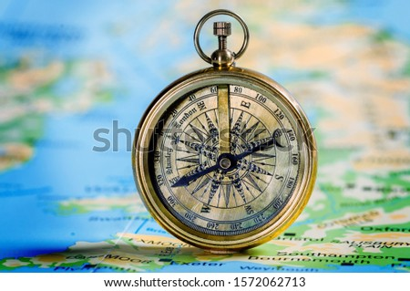 Magnetic compass  and location marking with a pin on routes on world map #1572062713