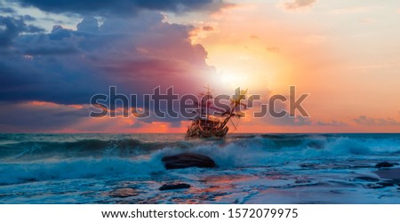 Sailing ship in storm sea at  sunset clouds