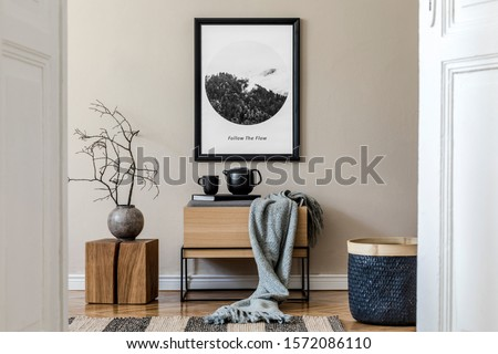 Modern scandinavian living room interior with black mock up poster frame, design commode,  leaf in vase, black rattan basket, books and elegant accessories. Template. Stylish home decor.  #1572086110