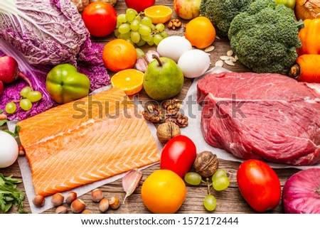 Trending paleo/pegan diet. Healthy balanced food concept. Set of fresh products, raw meat, salmon, vegetables and fruits. Old wooden boards background #1572172444