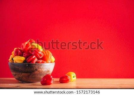 Colorful scotch bonnet chili peppers in wooden bowl over red background. Copy space Royalty-Free Stock Photo #1572173146