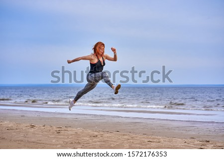 A middle aged woman with red hair jumps while jogging. A woman practices gymnastics on the sandy bank of a large river. Cloudy spring morning. #1572176353