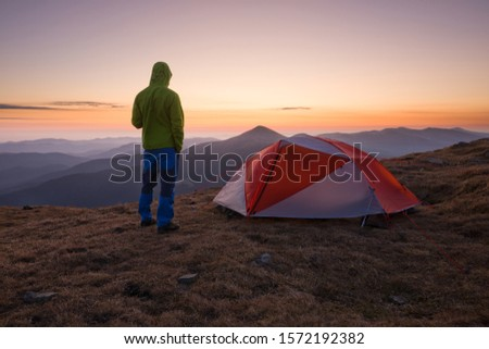 Hiker man in a hood standing near orange tent in the mountains at sunrise. Tourist enjoy mountain view. Travel concept. #1572192382