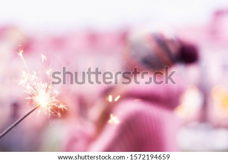 Burning Sparkler close-up and blurred silhouette of a happy girl in a pink sweater, scarf and hat with a pompom. The concept of Christmas and the new year. Soft focus. Selective focus. #1572194659
