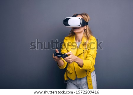 Caucasian woman in neutral casual outfit standing on a neutral grey background. She playing game using joystick with VR goggles and smiling happily. #1572209416