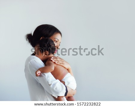 African American mum is comforting a baby on a white background. Royalty-Free Stock Photo #1572232822