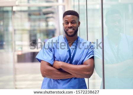 Portrait Of Male Doctor Wearing Scrubs Standing In Modern Hospital Building Royalty-Free Stock Photo #1572238627