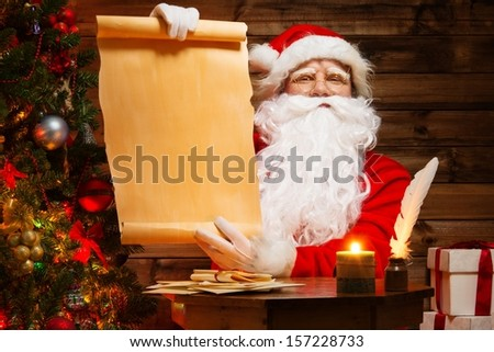 Santa Claus in wooden home interior holding blank wish list scroll #157228733