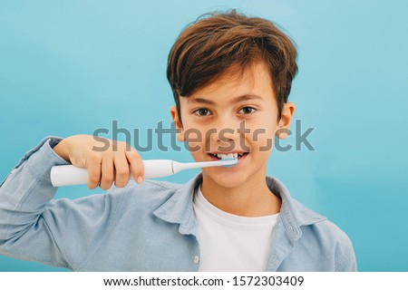 Mixed race little boy cleaning teeth with sonic toothbrush on blue background. Perfect removing plaque with cool toothbrush