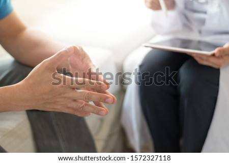 Doctor physician consulting with male patients in hospital exam room. Men's health concept #1572327118