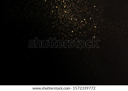 Gold glitter texture on a black background. Holiday background