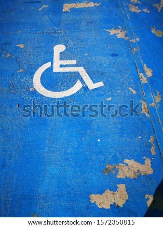 traditional icon for disabled zone only white paint on vivid blue surface #1572350815