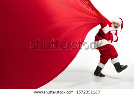 Santa Claus pulling huge bag full of christmas presents isolated on white background. Caucasian male model in traditional costume. New Year 2020, gifts, holidays, winter mood. Copyspace for your ad. #1572351169