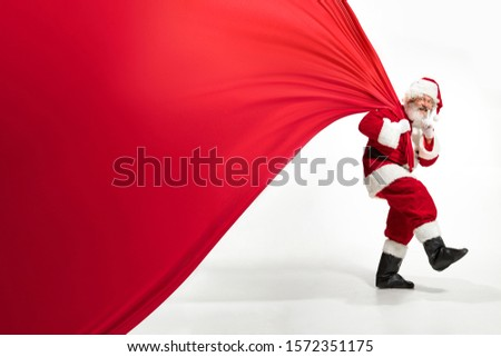 Santa Claus pulling huge bag full of christmas presents isolated on white background. Caucasian male model in traditional costume. New Year 2020, gifts, holidays, winter mood. Copyspace for your ad. #1572351175