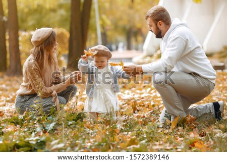 Family in a autumn park. Woman in a brown sweater. Cute newborn little girl with parents #1572389146