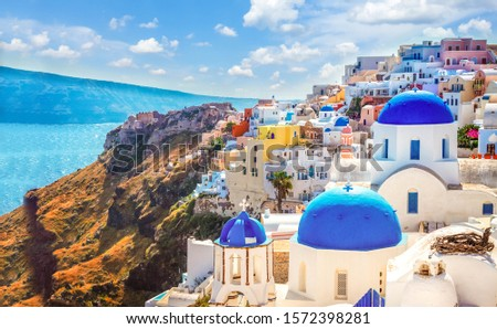Oia, traditional greek village of Santorini with blue domes of churches under sky with flowers, Greece, web banner format #1572398281