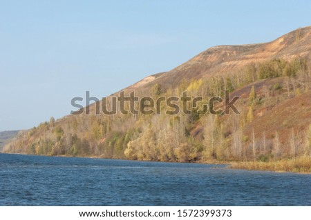 Autumn landscape, dark blue water, last warm days, river, trees, windy weather, yellow-red autumn leaves #1572399373