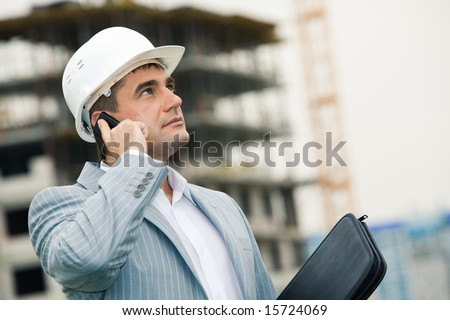 Image of serious engineer calling on his mobile and looking upwards at building site #15724069